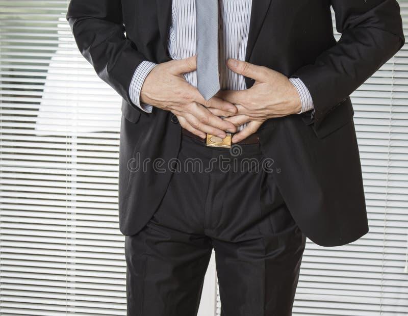 商人在痛苦中的握他的胃与stomachache或消化不良 库存图片