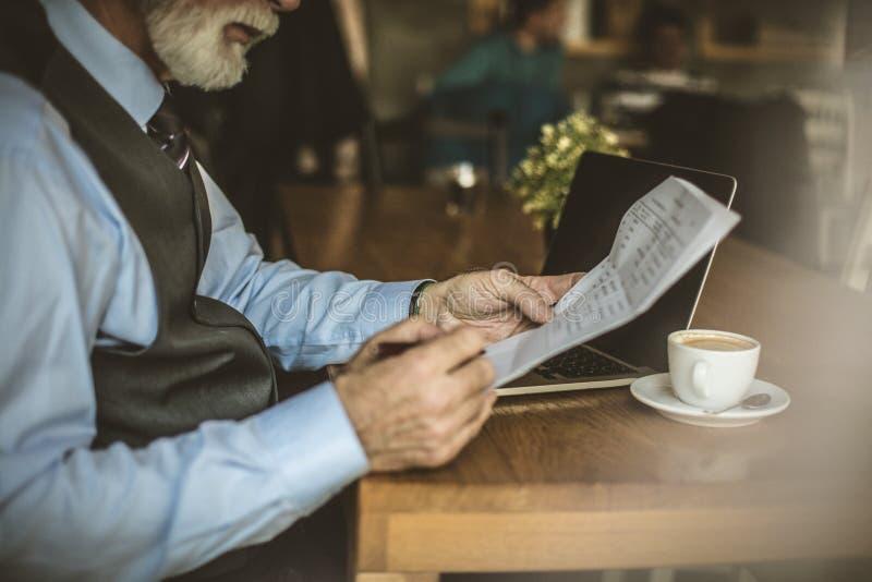 商人在研究他的膝上型计算机的咖啡店 免版税库存照片