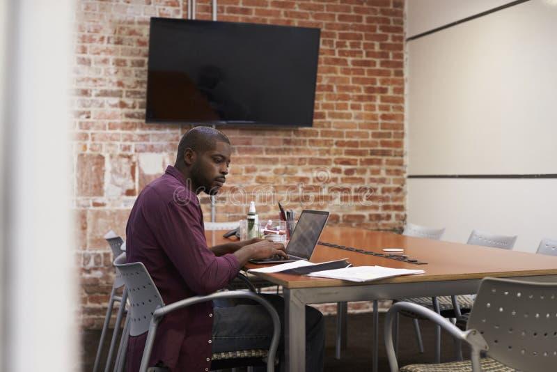 商人在研究膝上型计算机的会议室 库存图片