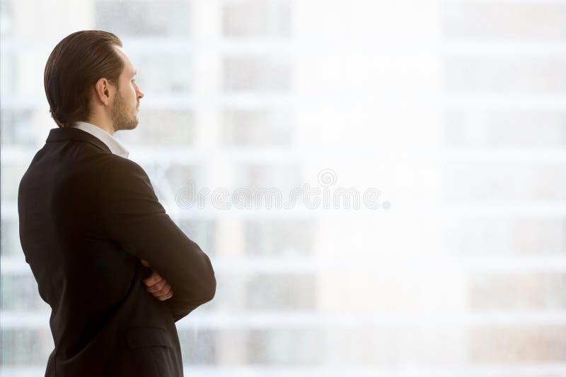 商人在窗口梦想看办公室 免版税库存图片