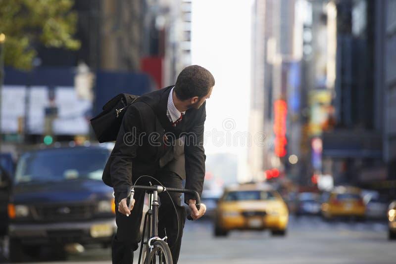 商人在都市街道上的骑马自行车 图库摄影