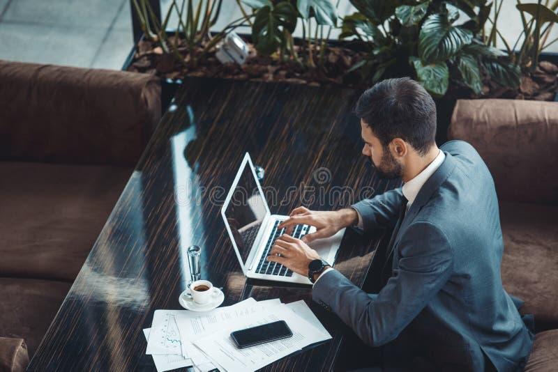商人在键入商业中心的餐馆坐膝上型计算机顶视图 免版税库存照片