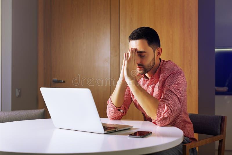 商人在他的个人计算机和prayingr的seet前面 免版税库存图片