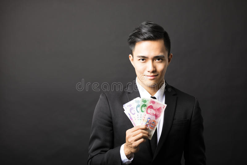 商人在他的手上的拿着元金钱 库存照片