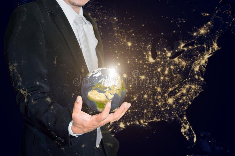 商人在他的手上的拿着小世界反对americ 库存图片