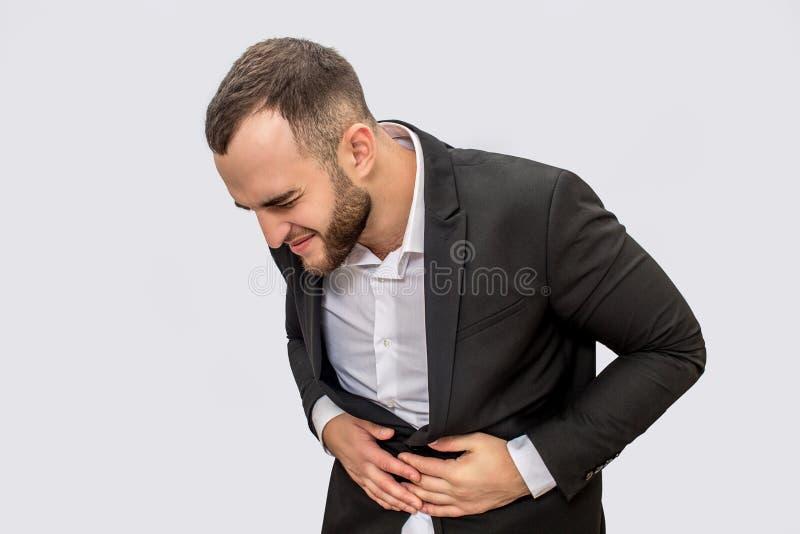 商人在stomack区域遭受痛苦 他握两只手那里并且看得下来 背景查出的白色 库存照片