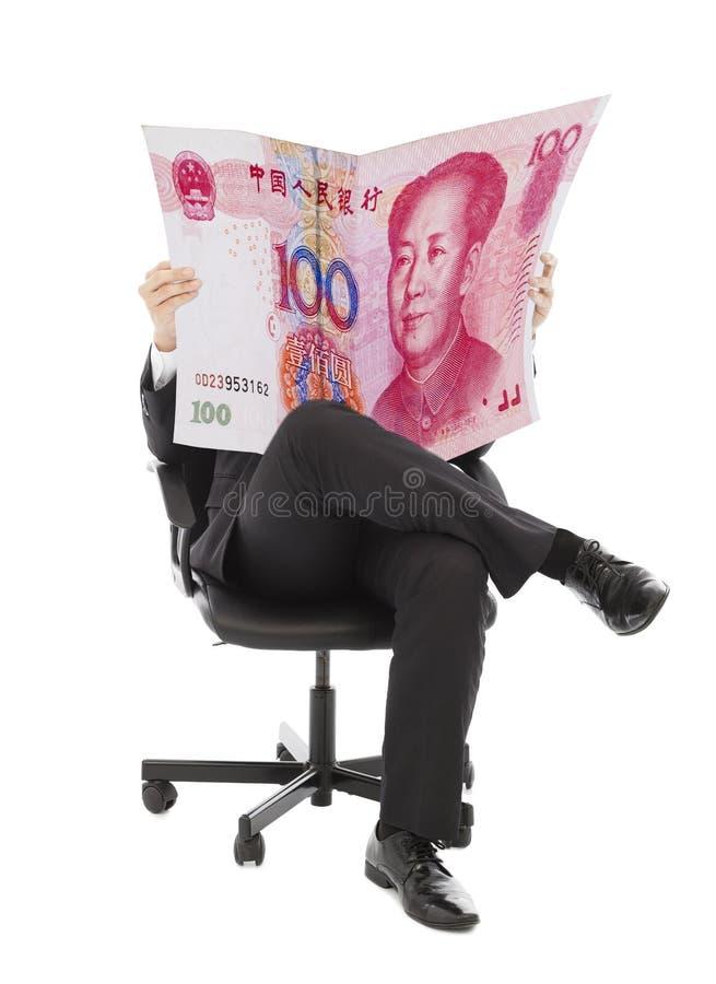商人坐与瓷货币的一把椅子 免版税库存照片