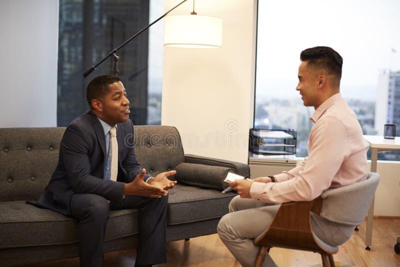 商人坐与男性顾问的长沙发会谈在办公室 库存图片