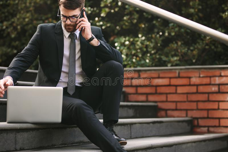 商人坐与膝上型计算机的步谈话在电话 库存图片