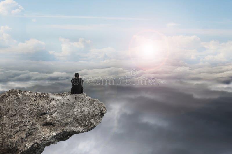 商人坐与自然天空白天cloudscap的峭壁 免版税图库摄影