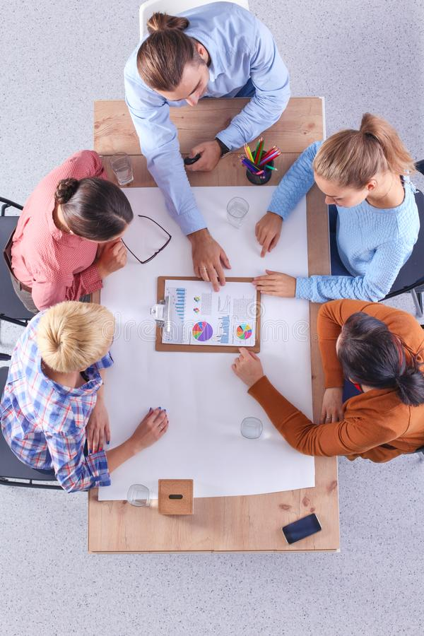 商人坐和谈论在会议上,在办公室 库存照片