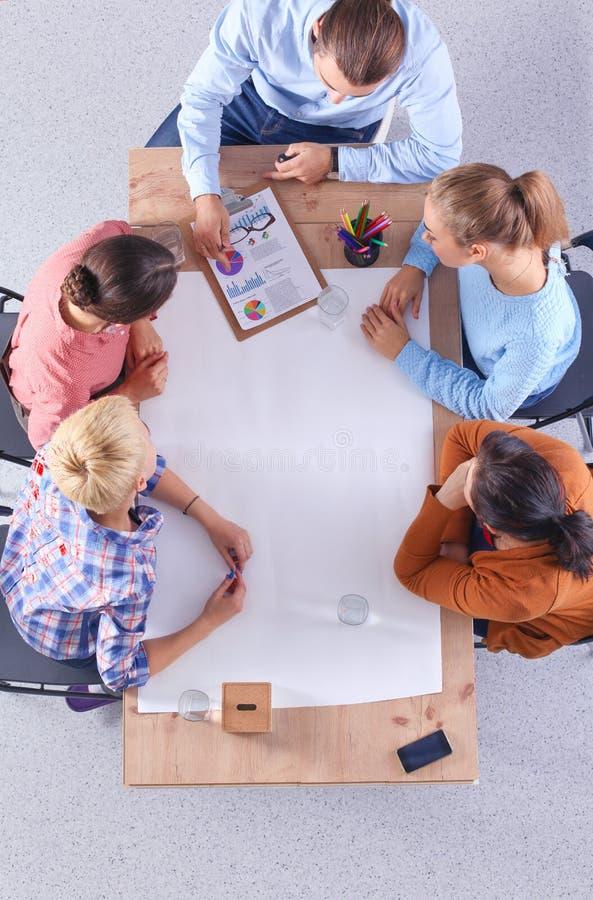 商人坐和谈论在会议上,在办公室 免版税库存照片