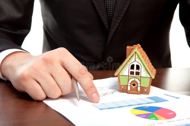坐在桌的商人和签合同 免版税库存照片