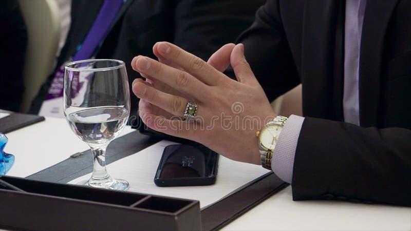 商人坐在他的手准备开始会议的书桌 股票 商人在会议上加入了他的手指 库存图片