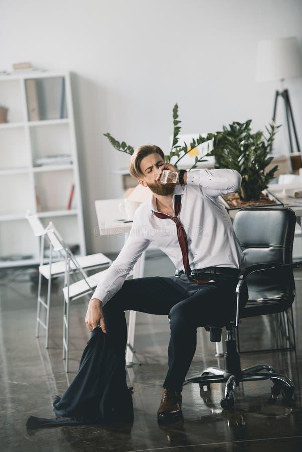 年轻商人坐椅子和饮用的威士忌酒从瓶在办公室 图库摄影