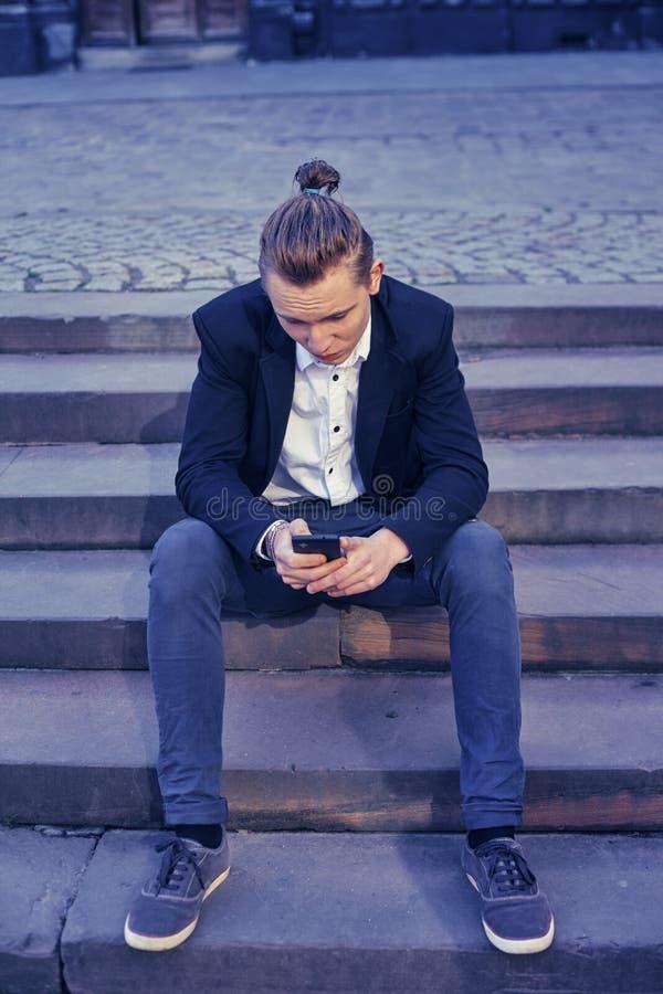 商人坐楼梯,沟通通过电话 免版税图库摄影