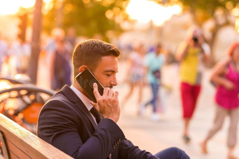 商人坐长凳和谈话在他的电话 库存照片
