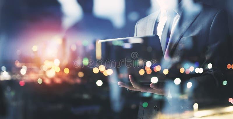 商人夜间与他的膝上型计算机一起使用 两次曝光 免版税库存图片