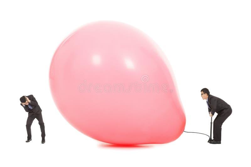 商人害怕的气球膨胀破裂 图库摄影