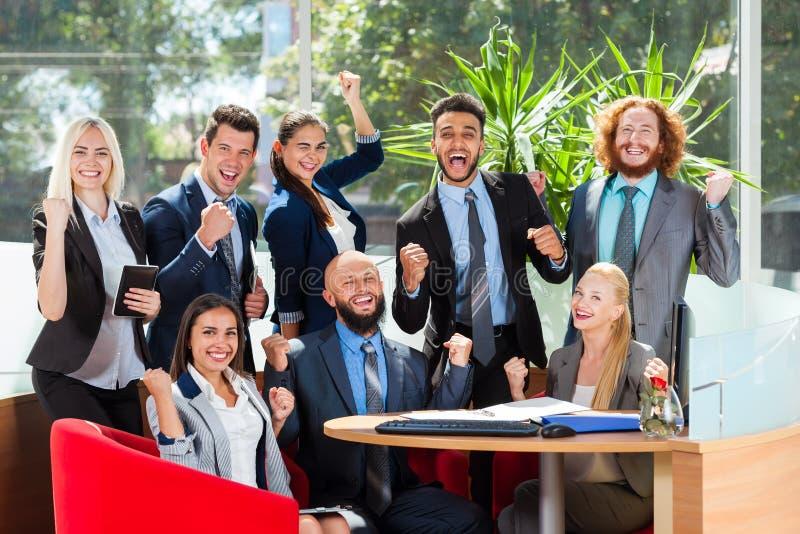 商人小组坐在书桌,成功的激动的队在现代办公室,与上升的买卖人愉快的微笑 库存图片