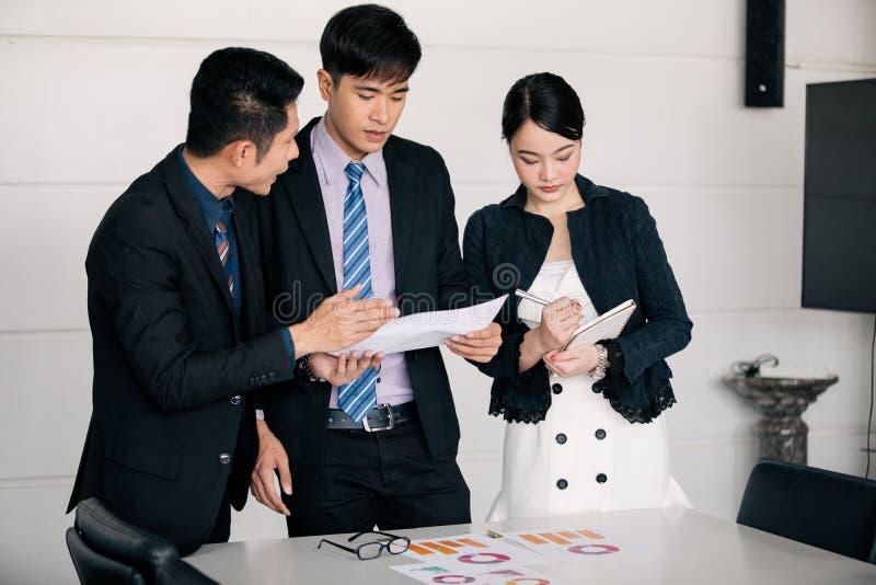 商人工作和点在图表财政图和分析文件在办公室桌上 免版税库存图片