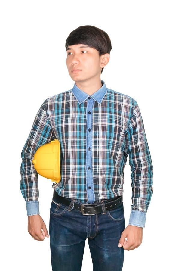 商人工程师举行黄色安全帽塑料和佩带在白色背景建筑概念的镶边衬衣蓝色 图库摄影