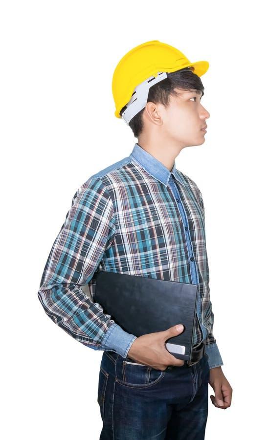 商人年轻举行手提电脑佩带在白色背景建筑概念的黄色安全帽塑料 免版税库存图片