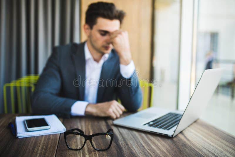 年轻商人强调了工作,关于工作的头疼在桌上 库存图片