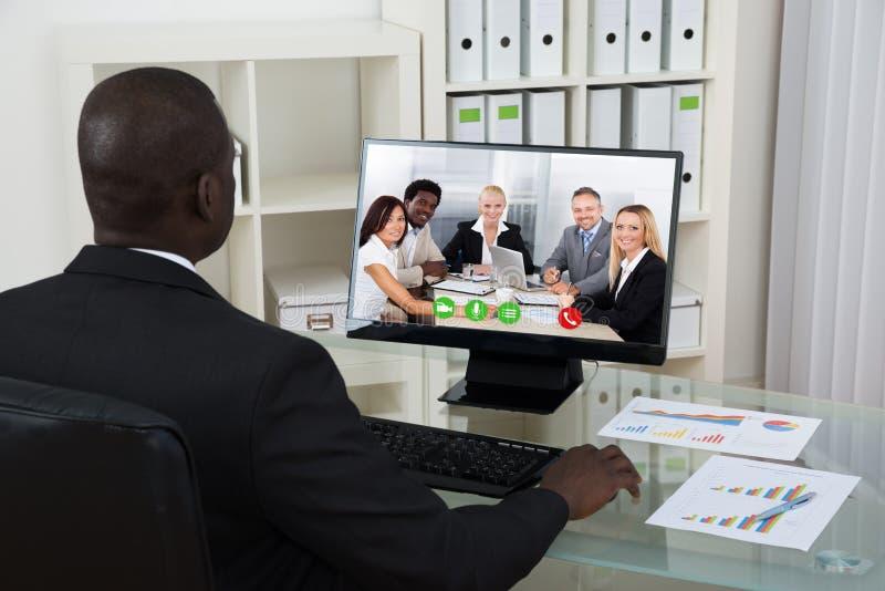 商人录影聊天与在计算机上的同事 库存照片