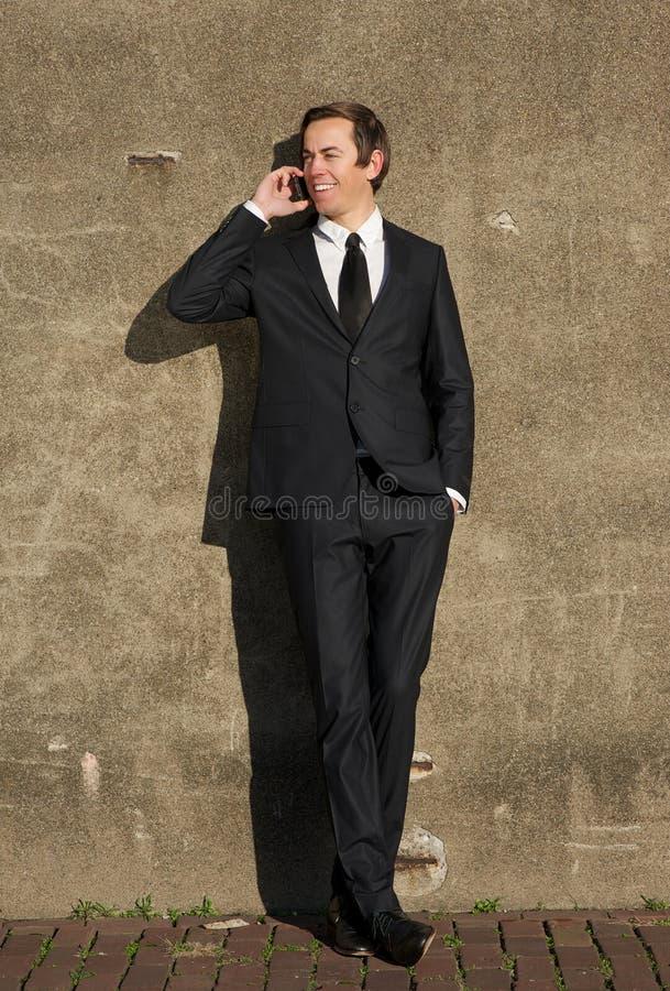 商人微笑和谈话在手机户外 库存图片