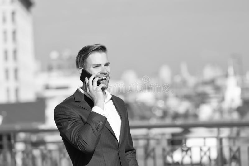 商人愉快的微笑的用途智能手机通信,地平线背景 衣服商人的人利用 免版税库存照片