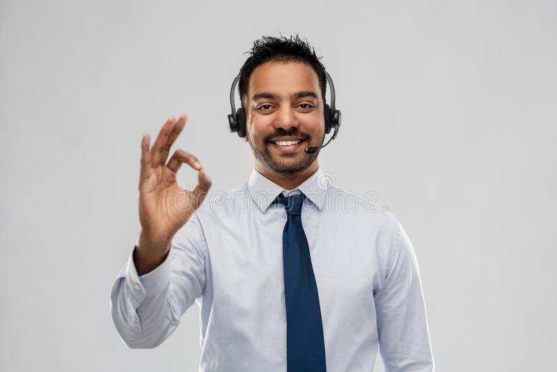商人或热线服务电话操作员陈列好标志 免版税库存照片