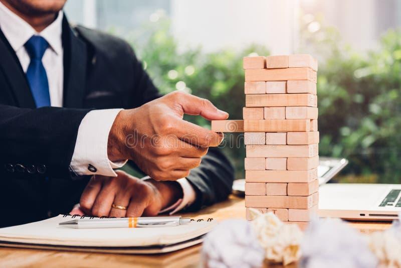 商人战略风险比赛拉扯在书桌上的塔式大楼木头  免版税库存图片