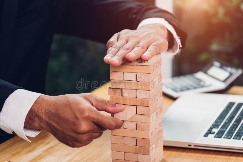 商人战略风险比赛拉扯在书桌上的塔式大楼木头  库存图片