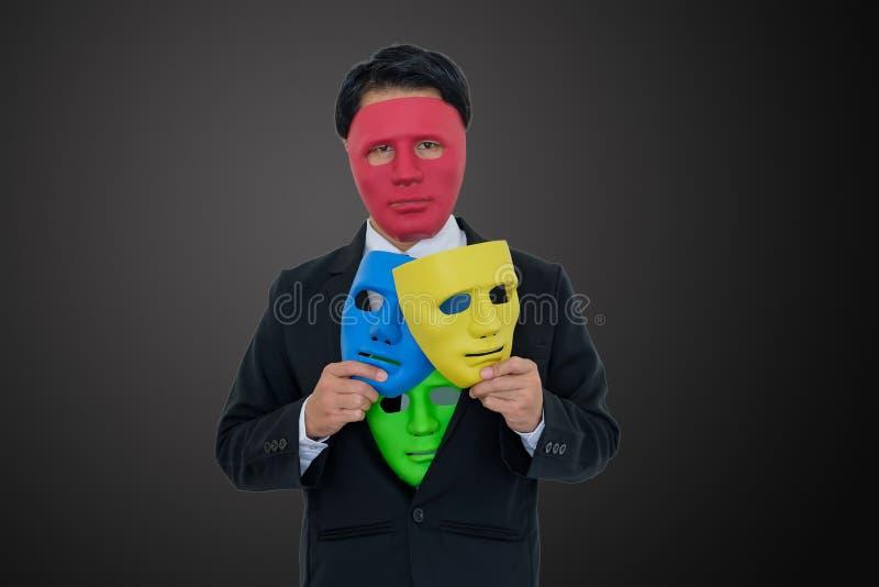 商人戴着红色面具并且在衣服掩藏许多面具 免版税库存图片