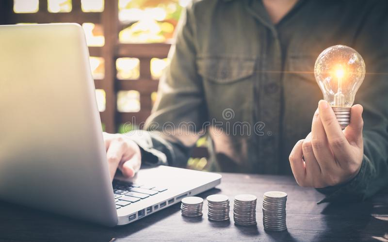 商人手在堆硬币的藏品电灯泡和与在工作场所的计算机一起使用 攒钱的创造性的想法概念 免版税库存图片
