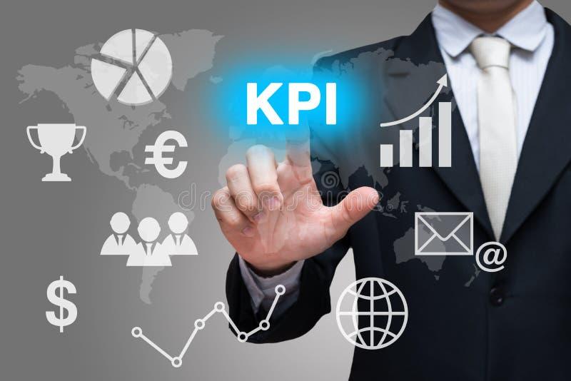 商人手在灰色背景的接触KPI标志 免版税库存图片