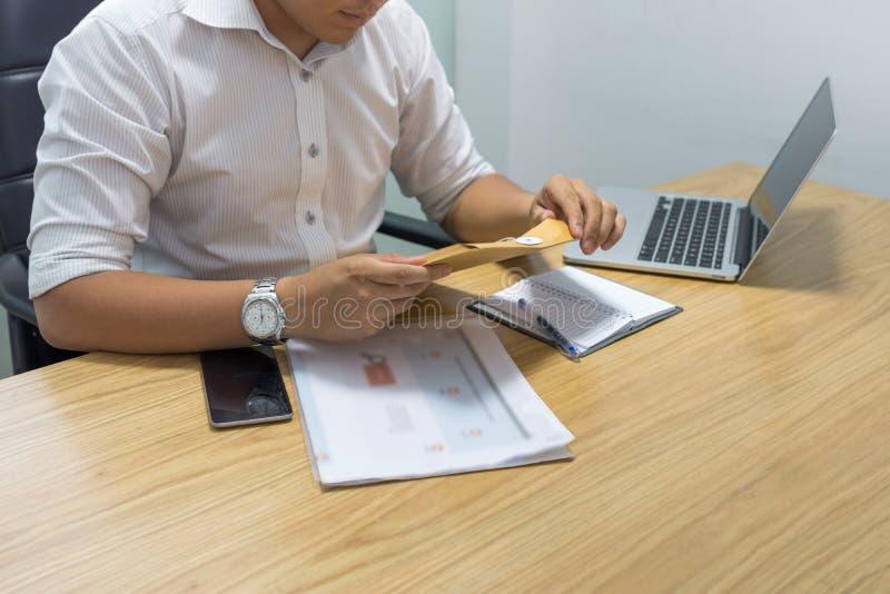 商人手开头信封在办公室 免版税库存图片