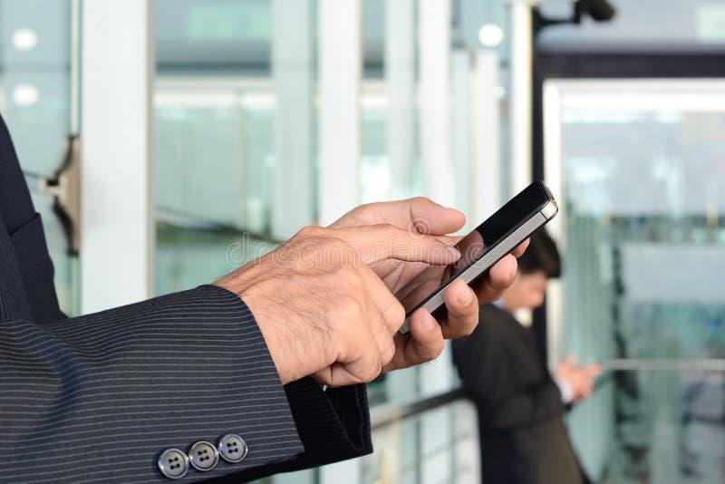 商人手感人的手机屏幕 免版税库存照片