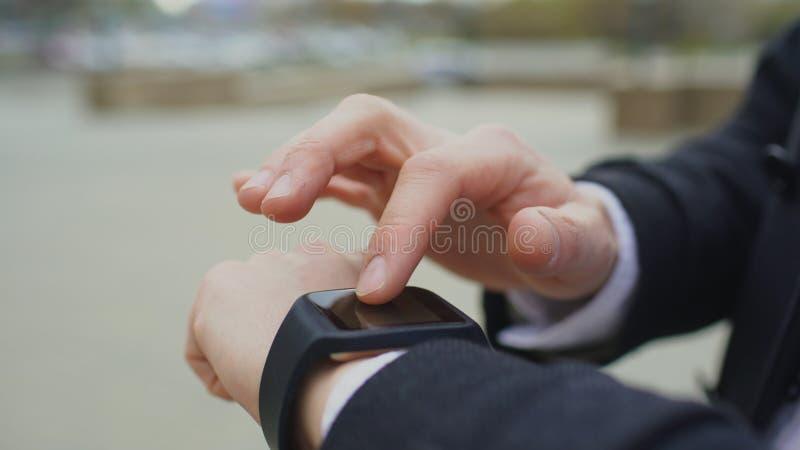 商人手特写镜头使用他的站立在街道上的smartwatch触摸屏幕的 库存图片