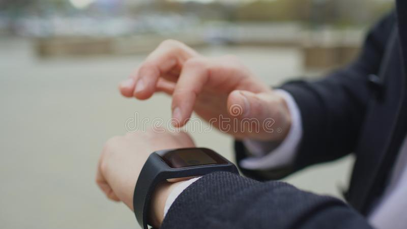 商人手特写镜头使用他的站立在街道上的smartwatch触摸屏幕的 库存照片