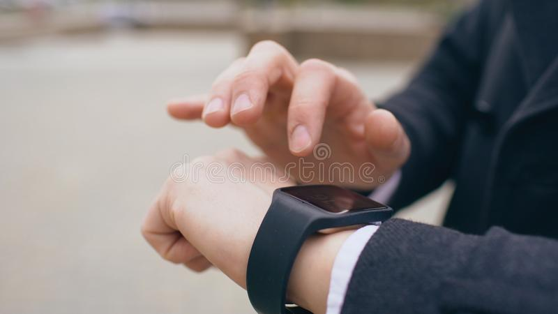 商人手特写镜头使用他的站立在街道上的smartwatch触摸屏幕的 免版税库存图片