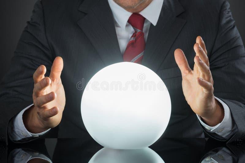 商人手特写镜头在水晶球的 库存照片