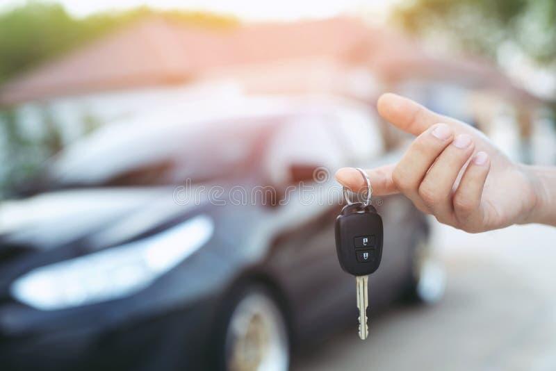 商人手藏品汽车钥匙前面与在背景的汽车 免版税库存照片