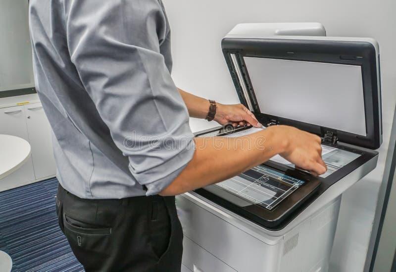 商人扫描重要和机要文件的用途打印机在办公室 免版税库存照片