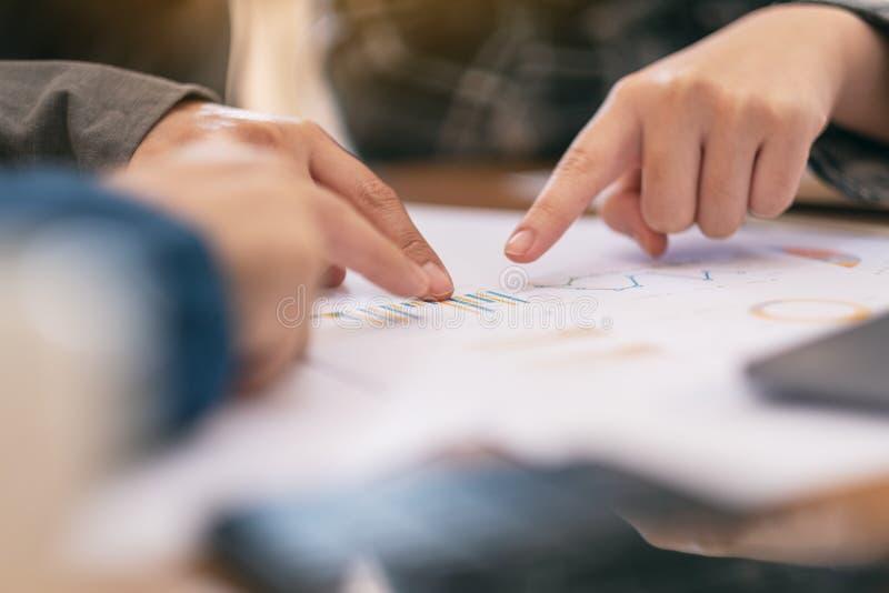 商人把手指指向的小组文书工作,当一起时谈论事务 库存图片