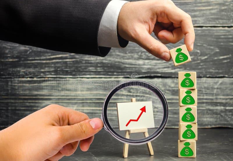 商人投入与美元的图片的一个块 资本积累和成功的事务 增加的预算和赢利 免版税图库摄影