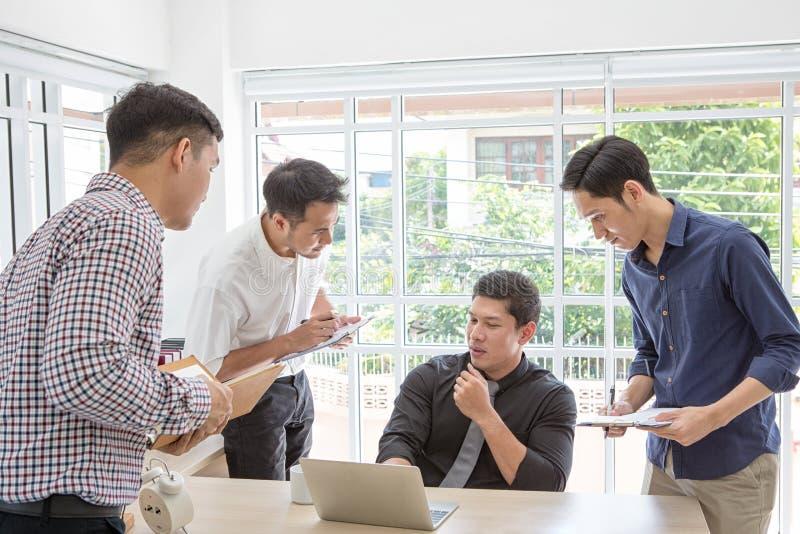 商人抱怨的数据在会议上 见面在书桌附近的商人 亚裔人员 商人年轻人 免版税库存照片