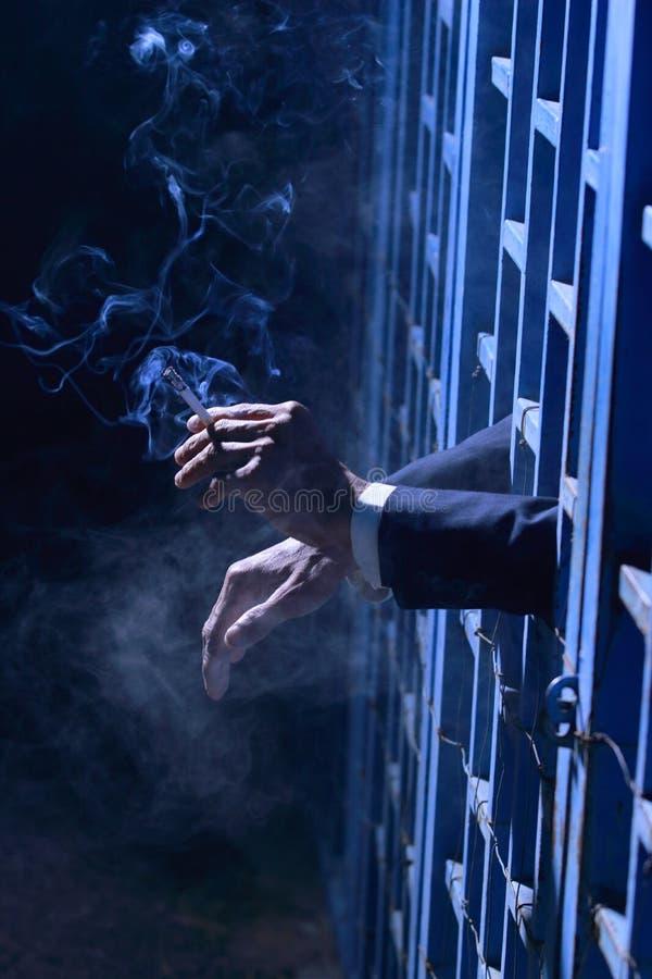 商人抽烟的手 免版税库存图片