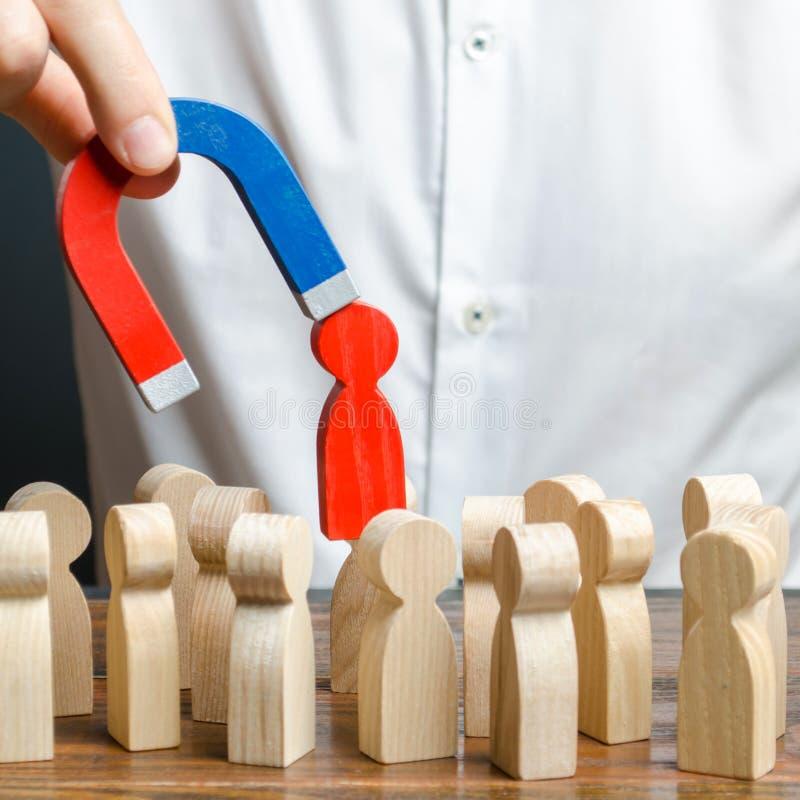 商人拔出一个红色图从人群的一个人在磁铁帮助下 领导处理事务并且形成队 免版税库存照片